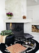 Tea break with pillows on a rug in front of a fireplace