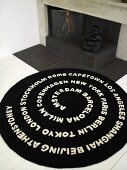 White letters on a black carpet in front of an open hearth (fireplace)
