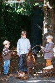 Three boys toasting marshmallows over an open fire