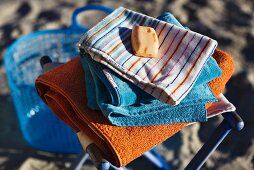Soap and a pile of towels on a beach stool