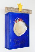 A blue, hand-painted wall cabinet