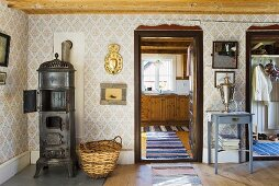 A living room in a country house - a fireplace against a papered wall and a view into the kitchen