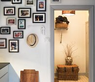 A collection of pictures hanging on the wall and a view into an illuminated hallway with a basket in front of the door