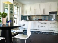 An open-plan kitchen - a view of a white fitted kitchen with stainless steel handles