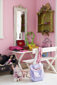 A corner of a child's room - a white bench and table in front of a mirror hanging on a pink wall