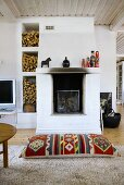 A floor cushion in front of a sooty fireplace and stack of firewood in a white stone shelf