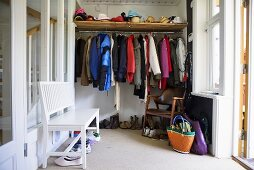 Dressing room - clothes rail with shelf and a white wooden bench