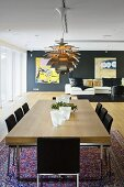 A dining table with a wooden top and designer lamp in an open-plan living-room-cum-dining-room with a view of a sofa