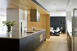 An open-plan kitchen - a shiny work surface and black drawers in front of a wooden partition wall and a view into a living room