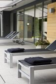 Designer loungers on a grey-tiled terrace in front of a house