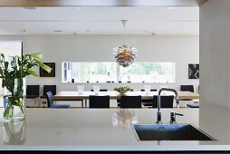 An open-plan kitchen - a sink in the kitchen counter and view of the dining table with a designer lamp