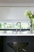 A kitchen counter - a sink with designer taps and a white shiny work surface