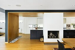 Open plan kitchen with fireplace in front of a black kitchen unit and white built in cupboard