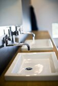Wall taps above wash basins built into a wooden counter