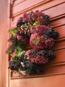 A wreath of red and blue berries on a wooden red door