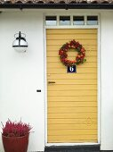A yellow door hung with a wreath of berries