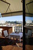 View of a roof terrace with set table under an awning and a view of a city