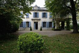 Old villa with blue window shutters on large grounds