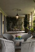 Light gray wicker furniture and planters on the loggia of a villa with lanterns hanging from the ceiling