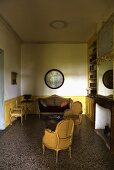 Half-darkened living room with the wood paneling and period furniture covered in yellow fabric