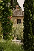 View of the natural stone facade of a Mediterranean home and a garden with cypresses