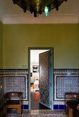 Moroccan lobby with a blue patterned tiles and open door