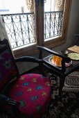 Upholstered chair and black side table in front of a window with parapet grid