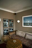 Living room corner with a sofa and photographs on a gray wall