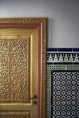 Carved wooden door and white and blue oriental wall tiles