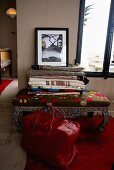 Red bags in front of an oriental style upholstered stool in front of a window