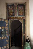 Oriental style painted door with a view of a stairway