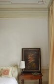 Corner of a bedroom -- a painting on a nightstand with a table lamp with a white shade