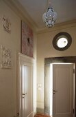 Hallway in a country home with a round transom window above the front door and a stone wall with natural color