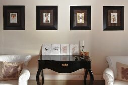 Black, shiny wall table in rococo style and a picture gallery
