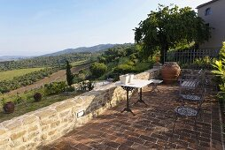 Terrace with a table and chairs on terracotta flooring with a view of the Mediterranean countryside