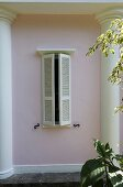 Window with wooden shutters and pink house facade with half columns