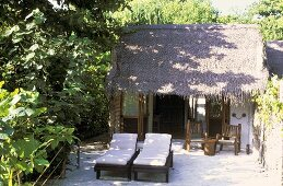House on the Maldives -- in the courtyard two lounge chairs with white cushion covers stand in front of a palm hut