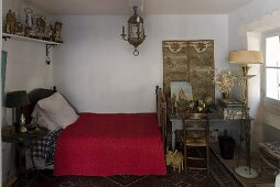 North African style bedroom with a red bedspread and table with floor lamp at the foot of the bed