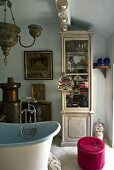 Corner of an oriental style bathroom with pink ottoman and glass fronted cabinet