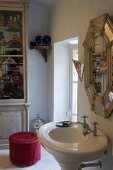 Corner of a bathroom -- pedestal sink with mirror and pink ottoman