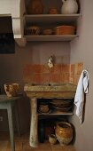 Rustic stone sink with terracotta wall tiles and bowls