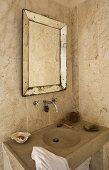 Tiled corner of a bathroom -- stone vanity with framed vintage style mirror