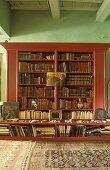 Mahogany bookcase against green wall