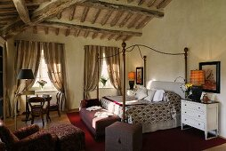Country style bedroom with rustic beam ceiling and elegant canopy beds