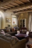 Living room in a country home with a rustic beam ceiling, beneath a cozy sitting room with leather ottomans