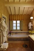 A built in bath tub in front of a window with patterned tiles and wooden ceiling in an attic