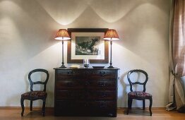 Dramatic wall lighting from two table lamps on an antique chest of drawers