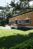Mediterranean villa with a red brick facade and terrace in a manicured garden