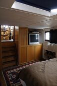 Cabin in a house boat with a built-in cupboard and stairs with a view of the steering wheel