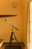 Antikes Fernrohr vor gelber Wand